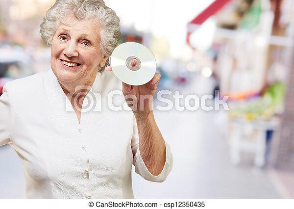 Mujer mayor sosteniendo CD - csp12350435