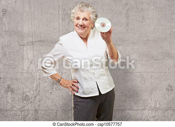Mujer mayor sosteniendo CD - csp10577757