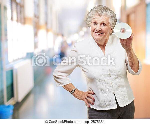 Mujer mayor sosteniendo CD - csp12575354