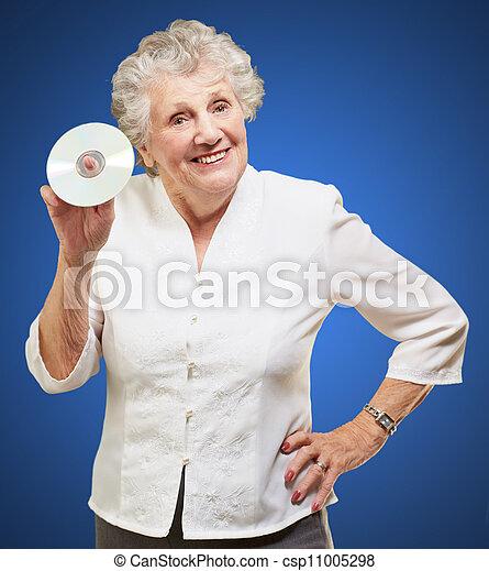 Mujer mayor sosteniendo CD - csp11005298