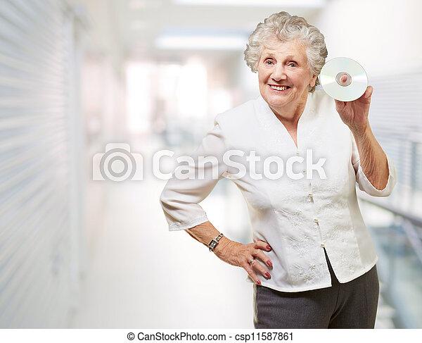 Mujer mayor sosteniendo CD - csp11587861