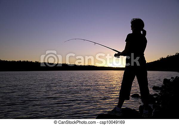 Una mujer pescando al atardecer - csp10049169