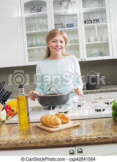 Retrato de linda joven haciendo panqueques en el ambiente de la cocina - csp42841564