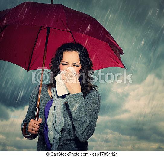 Mujer estornudo con paraguas sobre el fondo de la lluvia de otoño - csp17054424
