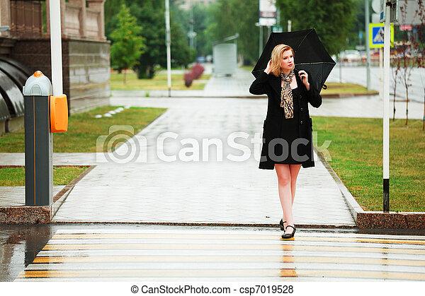 Mujer con paraguas bajo la lluvia - csp7019528