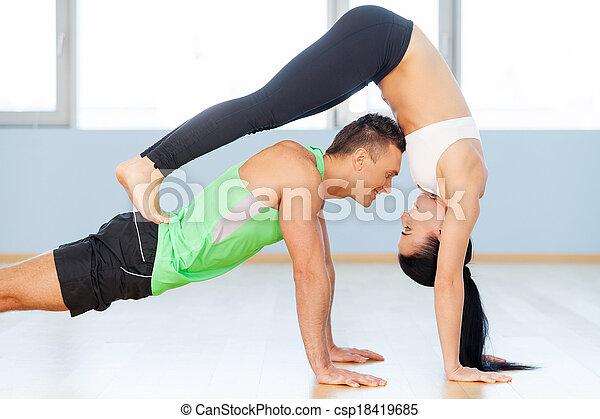 Hombre y mujer haciendo ejercicio. Una joven pareja amorosa haciendo ejercicio en el gimnasio - csp18419685