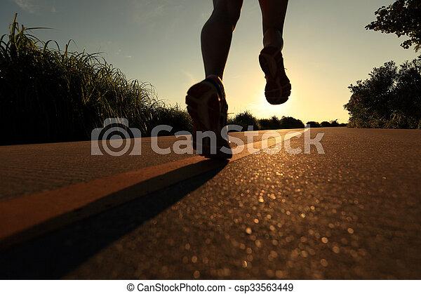 Piernas de mujer en forma joven corriendo en el sendero de la costa del amanecer - csp33563449