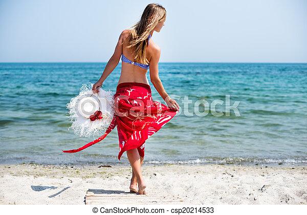 Una mujer camina por la playa - csp20214533