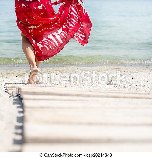 Una mujer camina por la playa - csp20214343