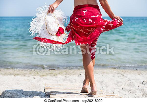 Una mujer camina por la playa - csp20218020
