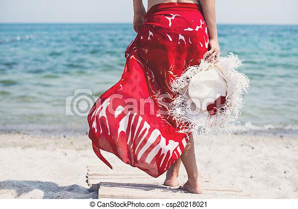 Una mujer camina por la playa - csp20218021