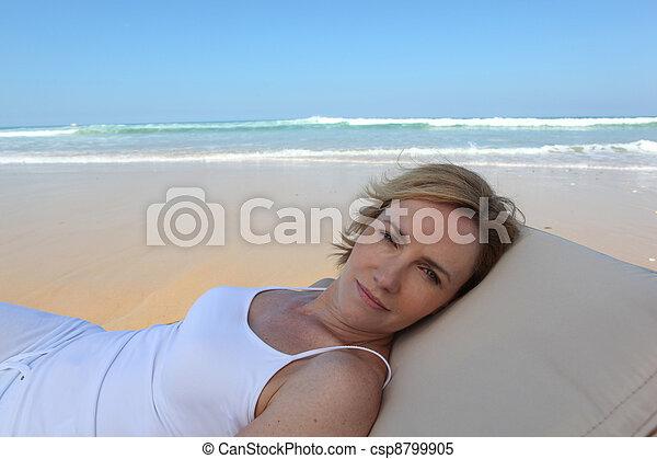 Mujer rubia relajada en la playa - csp8799905