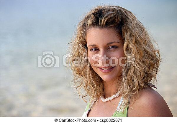 Rubia de pelo rizado en la playa - csp8822671