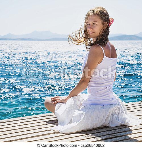 Una mujer sentada en la playa - csp26540802