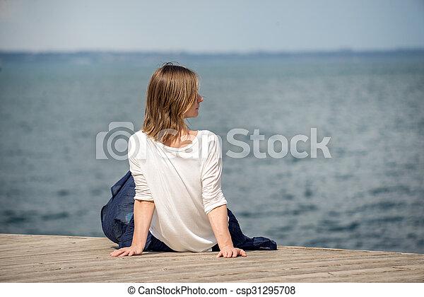 Una mujer sentada en la playa - csp31295708