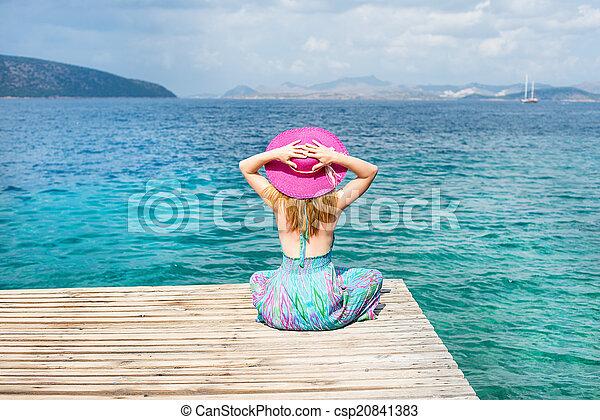 Una mujer sentada en la playa - csp20841383