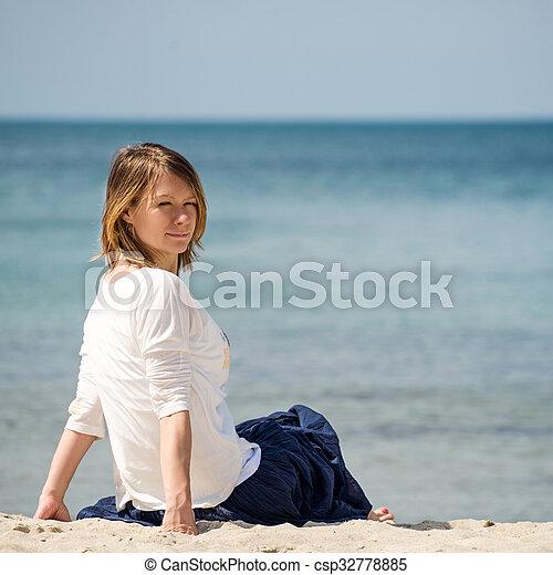 Una mujer sentada en la playa - csp32778885