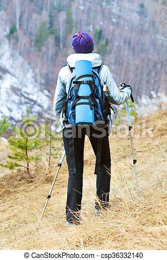 Una mujer joven caminando en el bosque a lo largo del sendero. - csp36332140