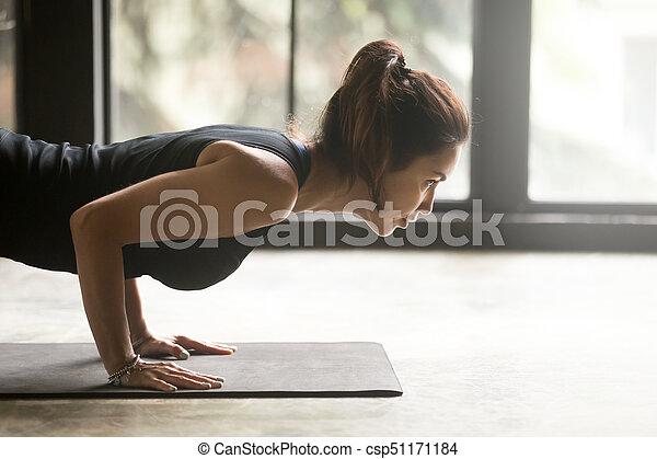 mujer joven y atractiva en pose chaturanga dandasana