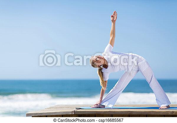 Mujer de mediana edad practicando yoga en la playa - csp16685567