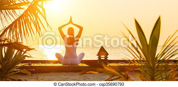 Una joven practicando yoga en la playa al atardecer - csp35690793