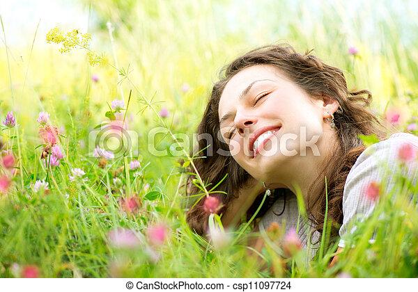 Una hermosa joven yaciendo en el prado de las flores. Disfruta de la naturaleza - csp11097724