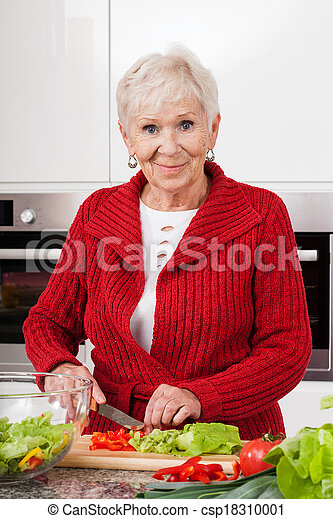 Mujer sonriente preparando la comida - csp18310001