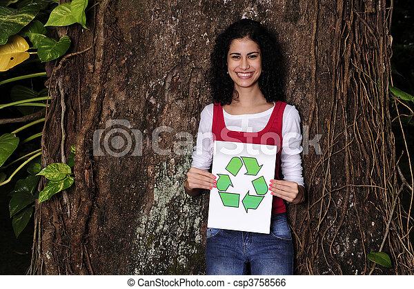 Reciclaje: mujer en el bosque sosteniendo una señal de reciclaje - csp3758566