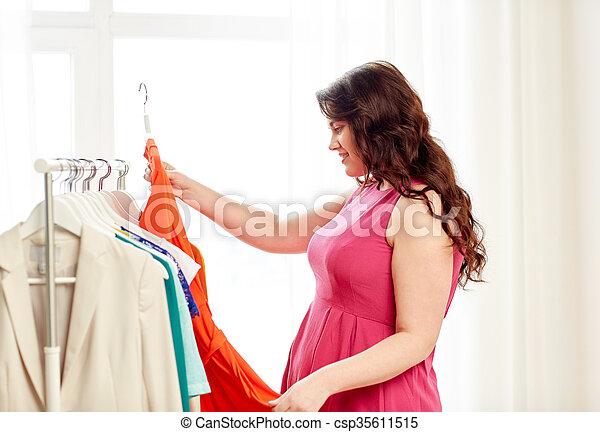 Feliz mujer de talla más eligiendo ropa en el vestuario - csp35611515