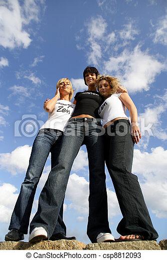 Tres mujeres se pararon en una gran roca en la playa - csp8812093