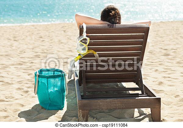 Mujer con máscara de buceo relajándose en la silla de cubierta en la playa - csp19111084