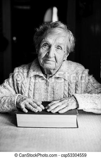 Una anciana con un libro cerrado sentado en la mesa. - csp53304559