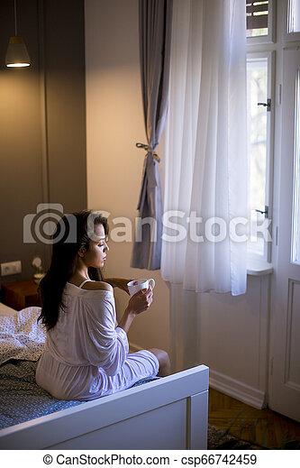 Mujer joven sentada en una cama con taza en el dormitorio - csp66742459