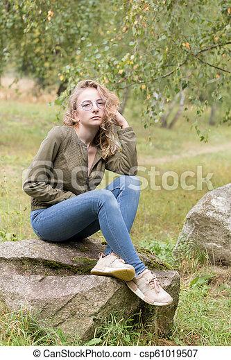 Una joven triste sentada en una roca en el bosque - csp61019507