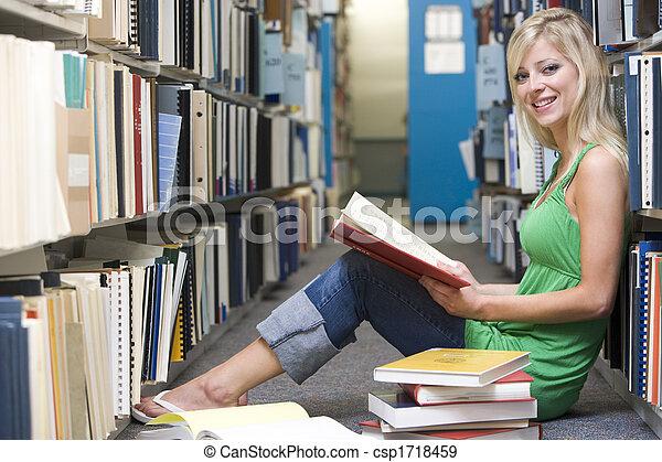 Una mujer sentada en el piso de la biblioteca - csp1718459