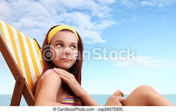 Mujer sentada en la playa pones el protector solar - csp26975905
