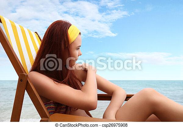 Mujer sentada en la playa pones el protector solar - csp26975908