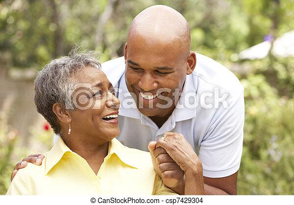 Mujer mayor abrazada por hijo adulto - csp7429304