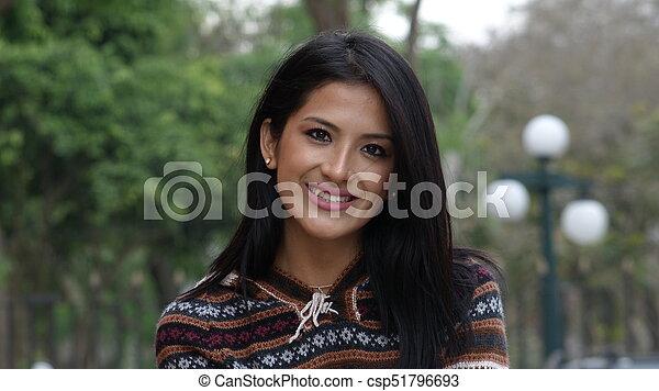Una joven sonriente afuera - csp51796693