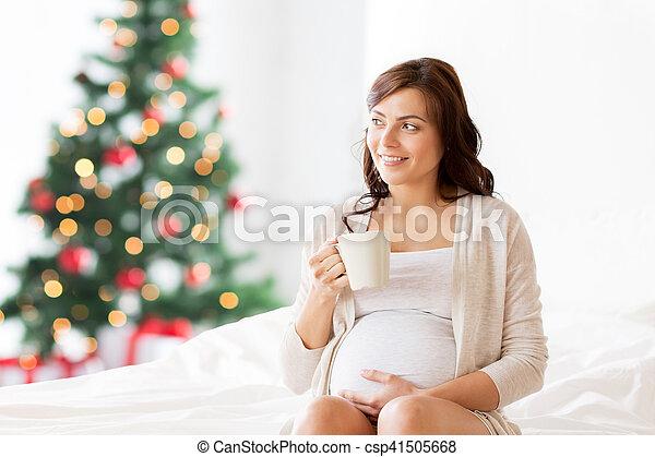 Mujer embarazada feliz con taza de té en Navidad - csp41505668