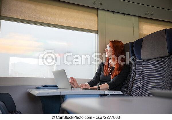 Una pelirroja sentada en el tren y trabajando con un portátil mirando por la ventana - csp72277868