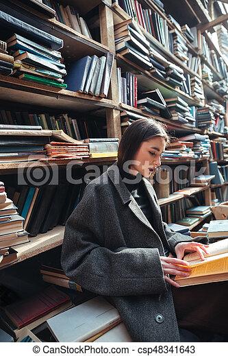 Retrato de una mujer leyendo libros en una vieja biblioteca - csp48341643