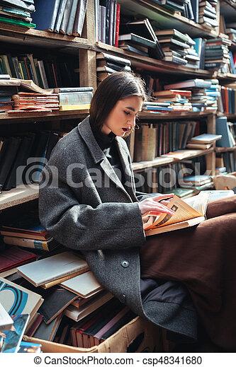Retrato de una mujer leyendo libros en una vieja biblioteca - csp48341680