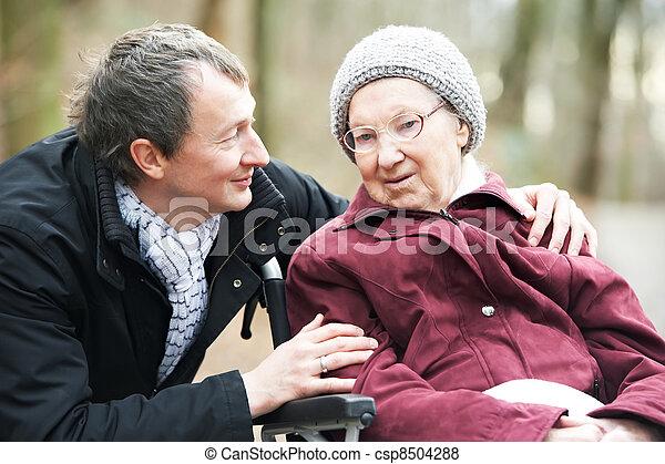 Una anciana en silla de ruedas con un hijo cuidadoso - csp8504288