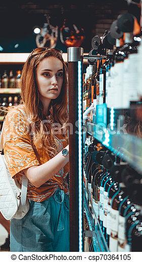La joven elige vino en el supermercado. - csp70364105