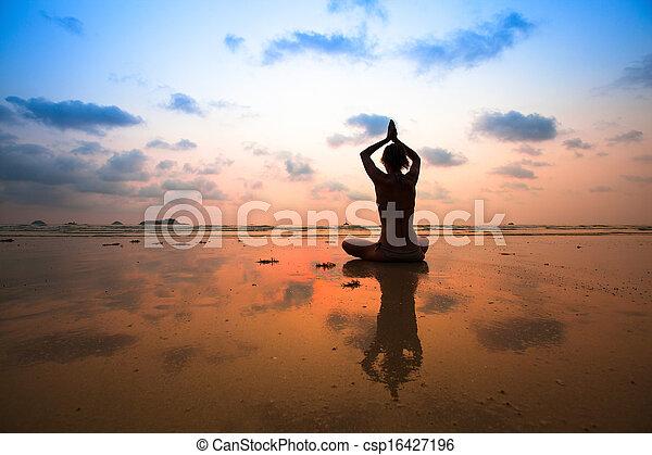 Yoga mujer sentada en loto posando en la playa durante el atardecer, reflexionando en el agua. - csp16427196