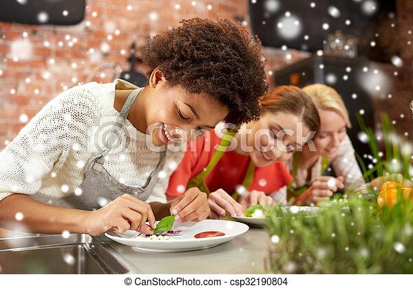 Mujeres felices cocinando y decorando platos - csp32190804