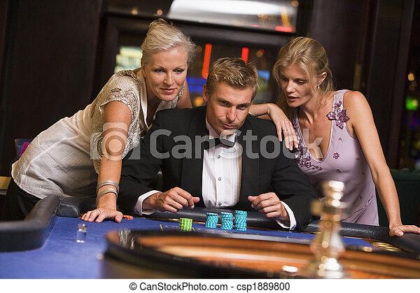 Hombre con mujeres glamorosas en el casino - csp1889800