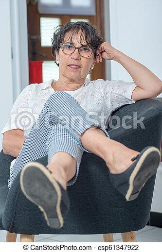 mulher bonita, sentando, poltrona, morena, maduras, lar - csp61347922