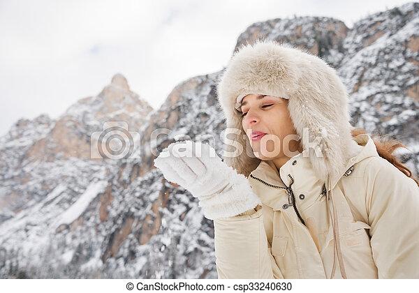 mulher, casaco pele, neve, mão, soprando, ao ar livre, chapéu branco - csp33240630